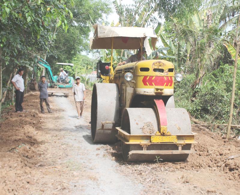 Xe cơ giới thi công san lắp nền hạ đường ĐX 06 xã Phú Đức.