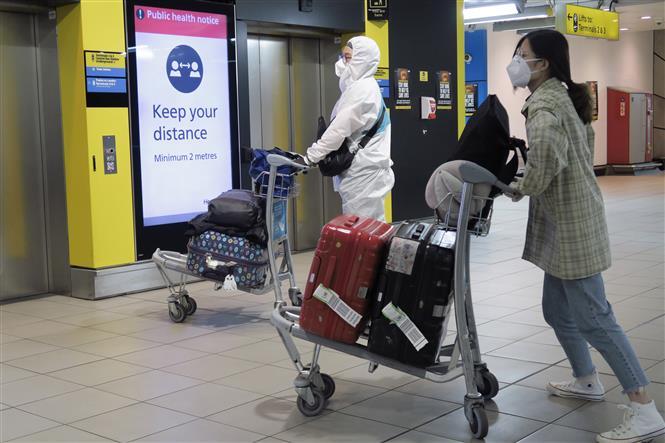 Hành khách đeo khẩu trang phòng lây nhiễm COVID-19 tại sân bay Heathrow ở London, Anh, ngày 1-5-2020. Ảnh: THX/TTXVN