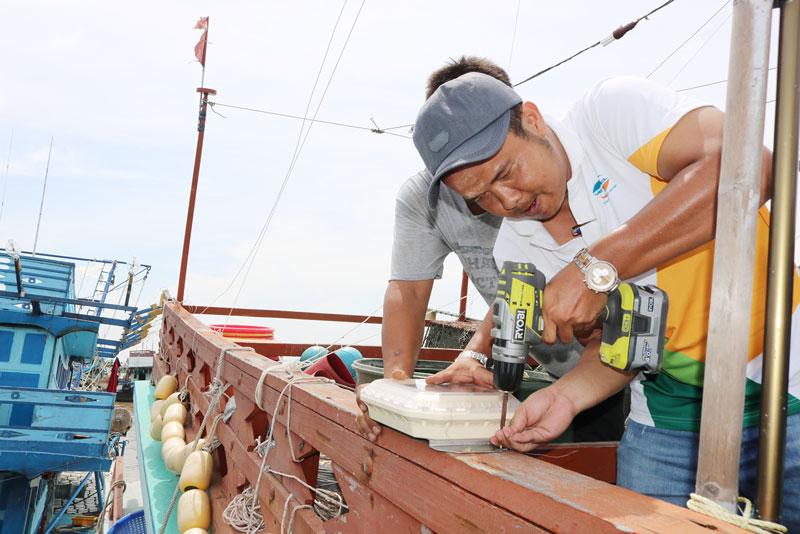 Lực lượng tiến hành lắp đặt thiết bị giám sát hành trình tàu cá.