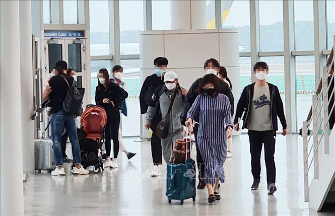 Hành khách đeo khẩu trang phòng lây nhiễm COVID-19 tại sân bay quốc tế Incheon, Hàn Quốc ngày 17-4-2020. Ảnh: Yonhap/TTXVN