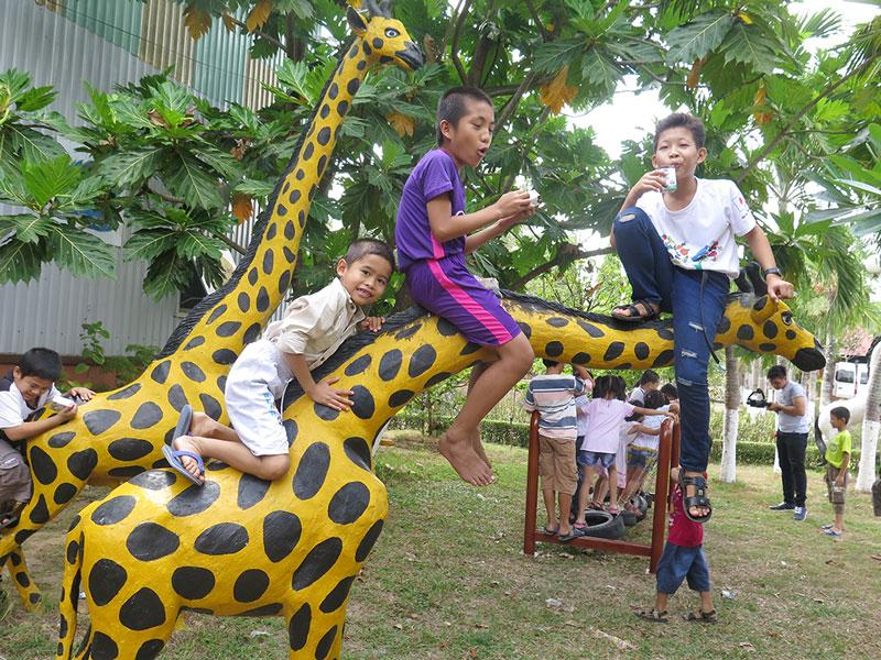 Trẻ em Làng SOS Bến Tre đùa vui và uống sữa do các nhà hảo tâm gởi tặng.