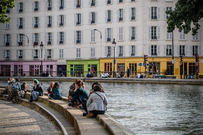 Người dân thư giãn bên sông Saint-Martin ở Paris, Pháp khi lệnh phong tỏa được nới lỏng, ngày 13-5-2020. Ảnh: THX/TTXVN