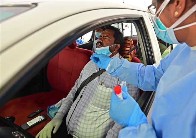Nhân viên y tế lấy mẫu dịch xét nghiệm COVID-19 cho người dân tại Abu Dhabi, UAE ngày 2-4-2020. Ảnh: AFP/ TTXVN