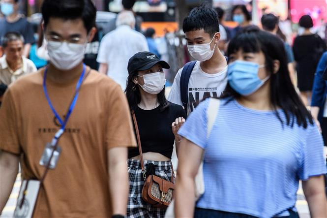 Người dân đeo khẩu trang phòng dịch COVID-19 tại Hong Kong, Trung Quốc ngày 13-5-2020. Ảnh: AFP/TTXVN