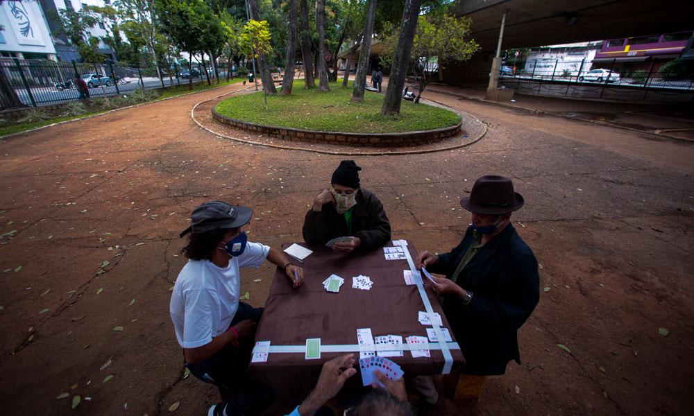 Người dân đeo khẩu trang chơi bài tại một quảng trường vắng vẻ ở Sao Paulo, Brazil ngày 7-5-2020. Ảnh: Getty Images