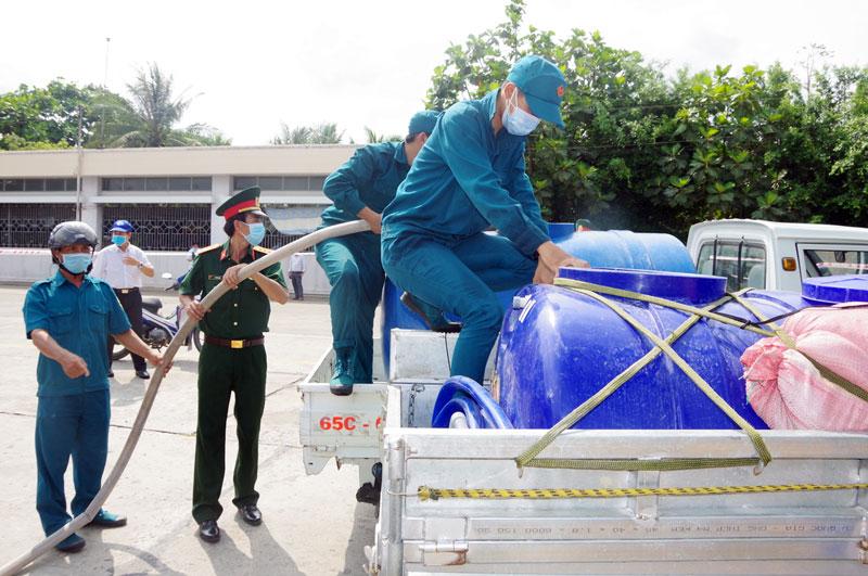 Đoàn thanh niên lực lượng vũ trang tỉnh hỗ trợ cấp nước ngọt cho bà con vùng hạn mặn. Ảnh: Đặng Thạch