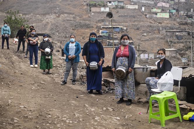Người dân gặp khó khăn do ảnh hưởng của dịch COVID-19 xếp hàng chờ nhận lương thực cứu trợ ở ngoại ô thủ đô Lima, Peru ngày 28-5-2020. Ảnh: AFP/TTXVN