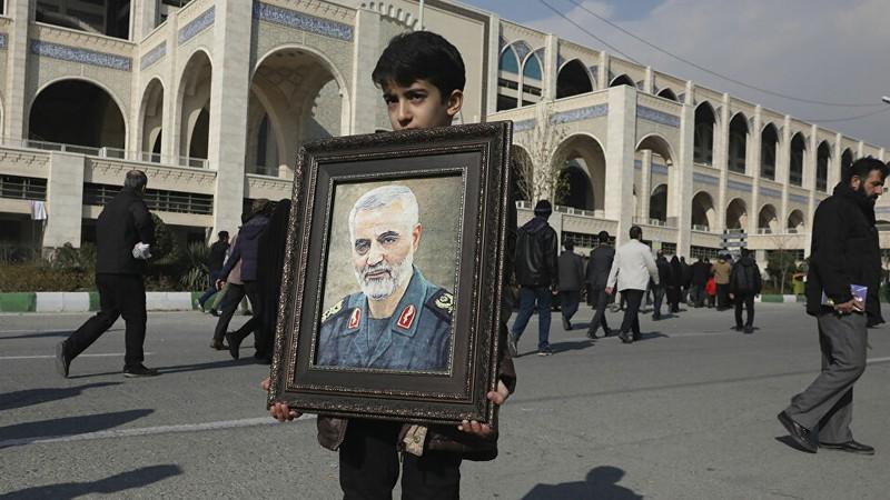 Một cậu bé mang ảnh chân dung của Tướng Soleimani. Ảnh: AP