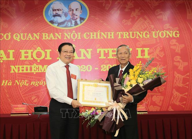 Đồng chí Phan Đình Trạc trao tặng Huy hiệu 50 tuổi Đảng cho đồng chí Trương Vĩnh Trọng. Ảnh: Doãn Tấn/TTXVN