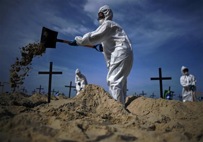 Nhóm tình nguyện đào huyệt mộ giả trên bãi biển Copacabana để tưởng nhớ những người đã tử vong vì dịch COVID-19 tại Rio de Janeiro, Brazil, ngày 11-6-2020. Ảnh: AFP/TTXVN