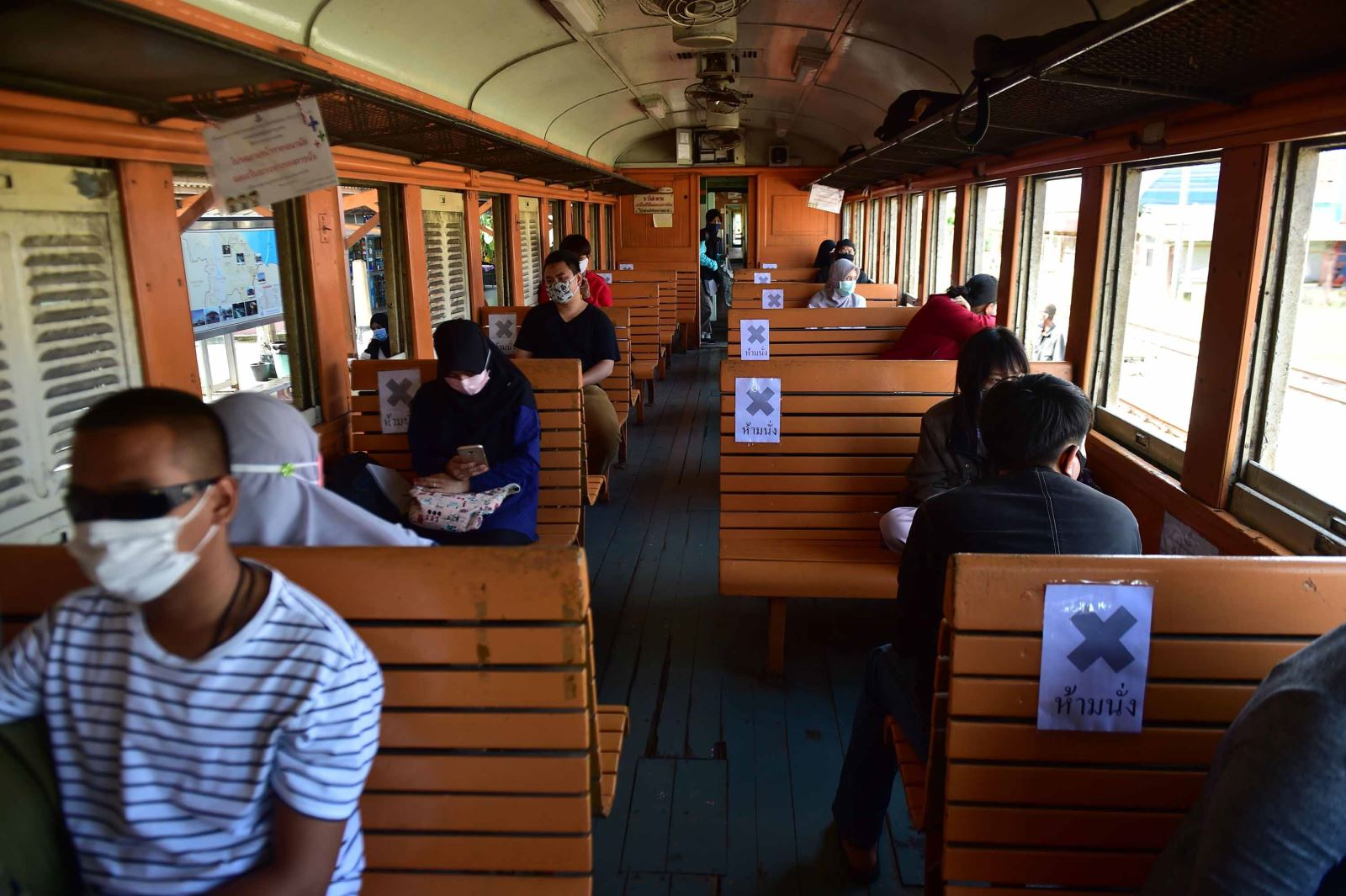 Passengers sit next to empty seats with social distancing signs on a train at Tanyong Mat railway station in the southern Thai province of Narathiwat, on June 11, following the lifting of coronavirus travel restrictions. Madaree Tohlala/AFP/Getty Images