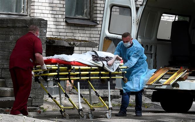 Nhân viên y tế chuyển bệnh nhân nghi mắc COVID-19 từ xe cứu thương vào một bệnh viện ở Saint Petersburg, Nga ngày 3-6-2020. Ảnh: AFP/TTXVN