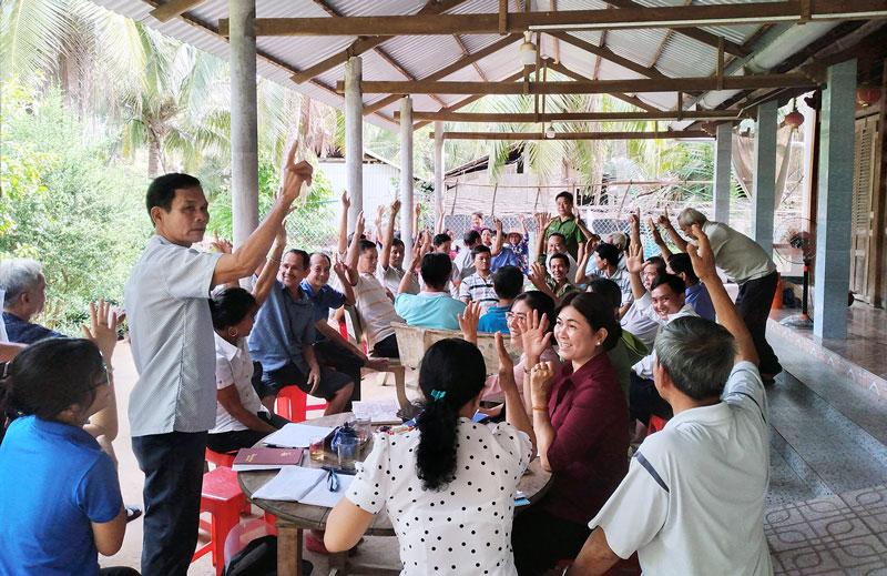 Người dân ấp Minh Nghĩa giơ tay đồng thuận hưởng ứng tiếp tục làm đường ĐC11. Ảnh: H. Đức