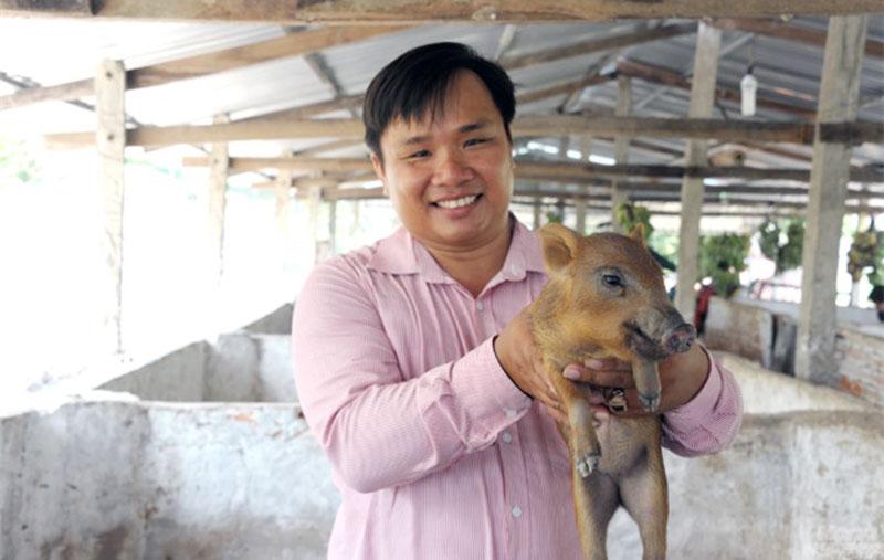 Đoàn Phan Dinh cẩn thận chăm sóc đàn heo.