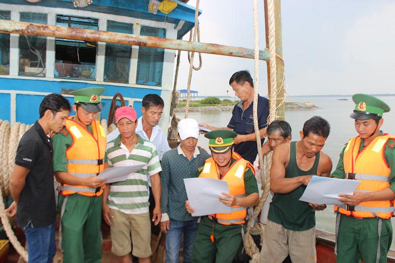 Cán bộ, chiến sĩ Đồn Biên phòng Cửa Đại tuyên truyền pháp luật về biển đảo cho ngư dân.