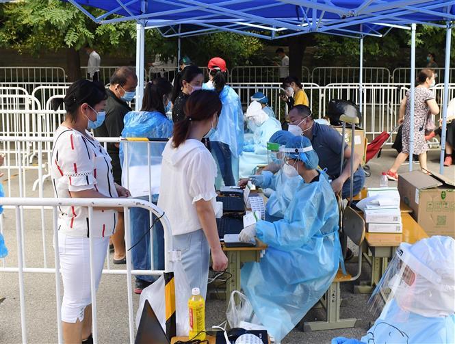 Nhân viên y tế lấy mẫu dịch xét nghiệm COVID-19 cho người dân ở Bắc Kinh, Trung Quốc ngày 26-6-2020. Ảnh: THX/ TTXVN
