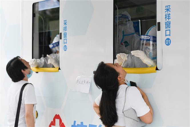 Nhân viên y tế lấy mẫu dịch xét nghiệm COVID-19 cho người dân tại Bắc Kinh, Trung Quốc, ngày 28-6-2020. Ảnh: THX/ TTXVN