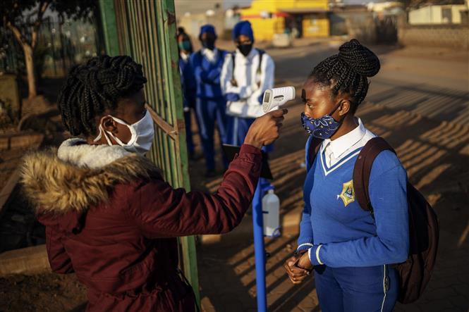 Kiểm tra thân nhiệt cho học sinh tại trường học ở Tembisa, Ekurhuleni, Nam Phi ngày 8-6-2020. Ảnh: AFP/ TTXVN