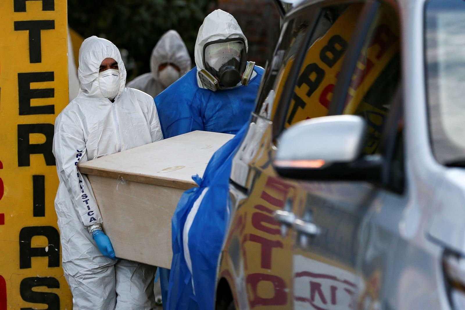 Cảnh sát và nhân viên tang lễ di chuyển quan tài nạn nhân COVID-19 ở Quito, Ecuador. Ảnh: EPA-EFE