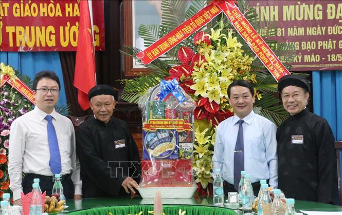 Phó Chủ tịch - Tổng Thư ký Ủy ban Trung ương MTTQ Việt Nam Hầu A Lềnh (thứ 2 từ phải qua) tặng quà chúc mừng đại lễ kỷ niệm 81 năm Ngày khai sáng đạo Phật giáo Hòa Hảo.