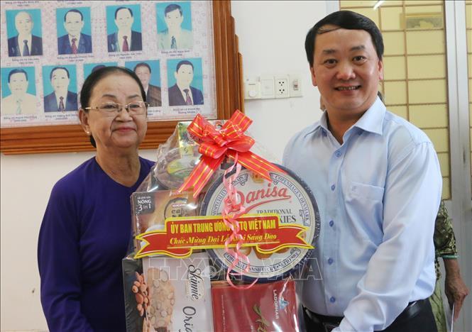 Phó Chủ tịch - Tổng Thư ký Ủy ban Trung ương MTTQ Việt Nam Hầu A Lềnh (bìa phải) tặng quà gia đình chính sách là đồng bào Phật giáo Hòa Hảo tiêu biểu trên đại bàn huyện Phú Tân (An Giang) nhân đại lễ kỷ niệm 81 năm Ngày khai sáng đạo Phật giáo Hòa Hảo.