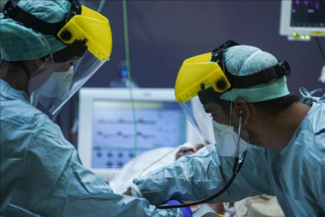 Nhân viên y tế chăm sóc bệnh nhân nhiễm COVID-19 tại bệnh viện ở Brussels, Bỉ ngày 25/3. Ảnh: AFP/TTXVN