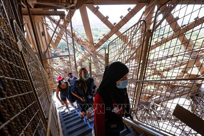 Du khách tham quan Tháp Eiffel tại thủ đô Paris, Pháp ngày 25/6. Ảnh: AFP/TTXVN