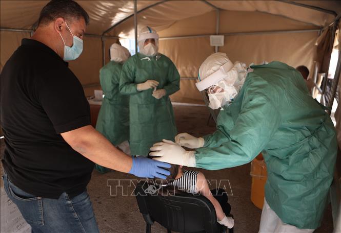 Nhân viên y tế lấy mẫu dịch xét nghiệm COVID-19 cho người dân tại thành phố Hebron, Bờ Tây ngày 22/6. Ảnh: THX/TTXVN