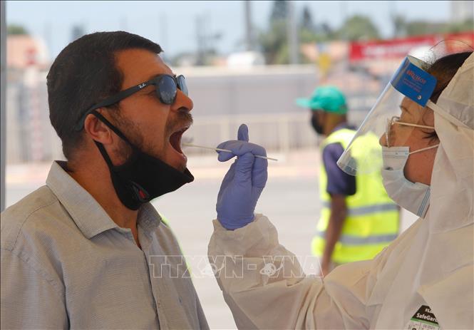 Nhân viên y tế lấy mẫu dịch xét nghiệm COVID-19 cho người dân tại Lod, Israel ngày 9/7. Ảnh: THX/TTXVN