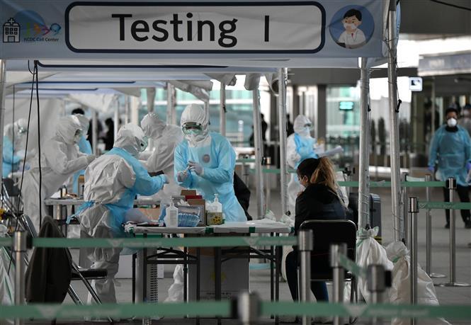Nhân viên y tế lấy mẫu dịch xét nghiệm COVID-19 cho hành khách tại sân bay quốc tế Incheon, phía tây thủ đô Seoul, Hàn Quốc, ngày 1-4-2020. Ảnh: AFP/ TTXVN