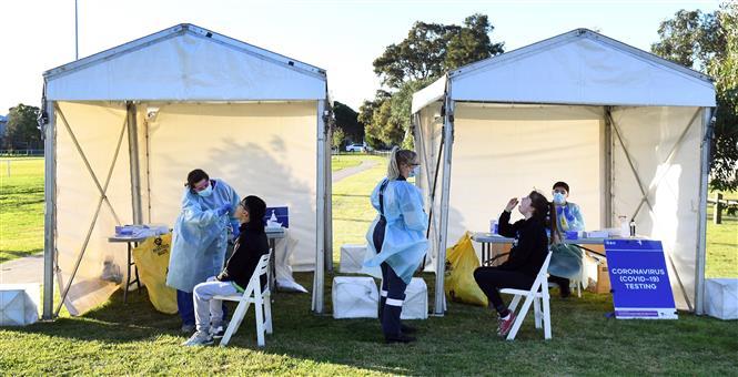 Nhân viên y tế lấy mẫu dich xét nghiệm COVID-19 cho người dân tại Melbourne, Australia, ngày 1-7-2020. Ảnh: AFP/ TTXVN