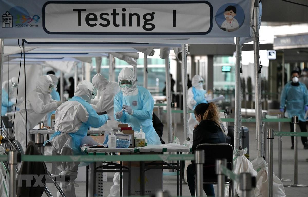 Nhân viên y tế lấy mẫu dịch xét nghiệm COVID-19 cho hành khách tại sân bay quốc tế Incheon, phía tây thủ đô Seoul, Hàn Quốc, ngày 1-4-2020. Ảnh: AFP/TTXVN