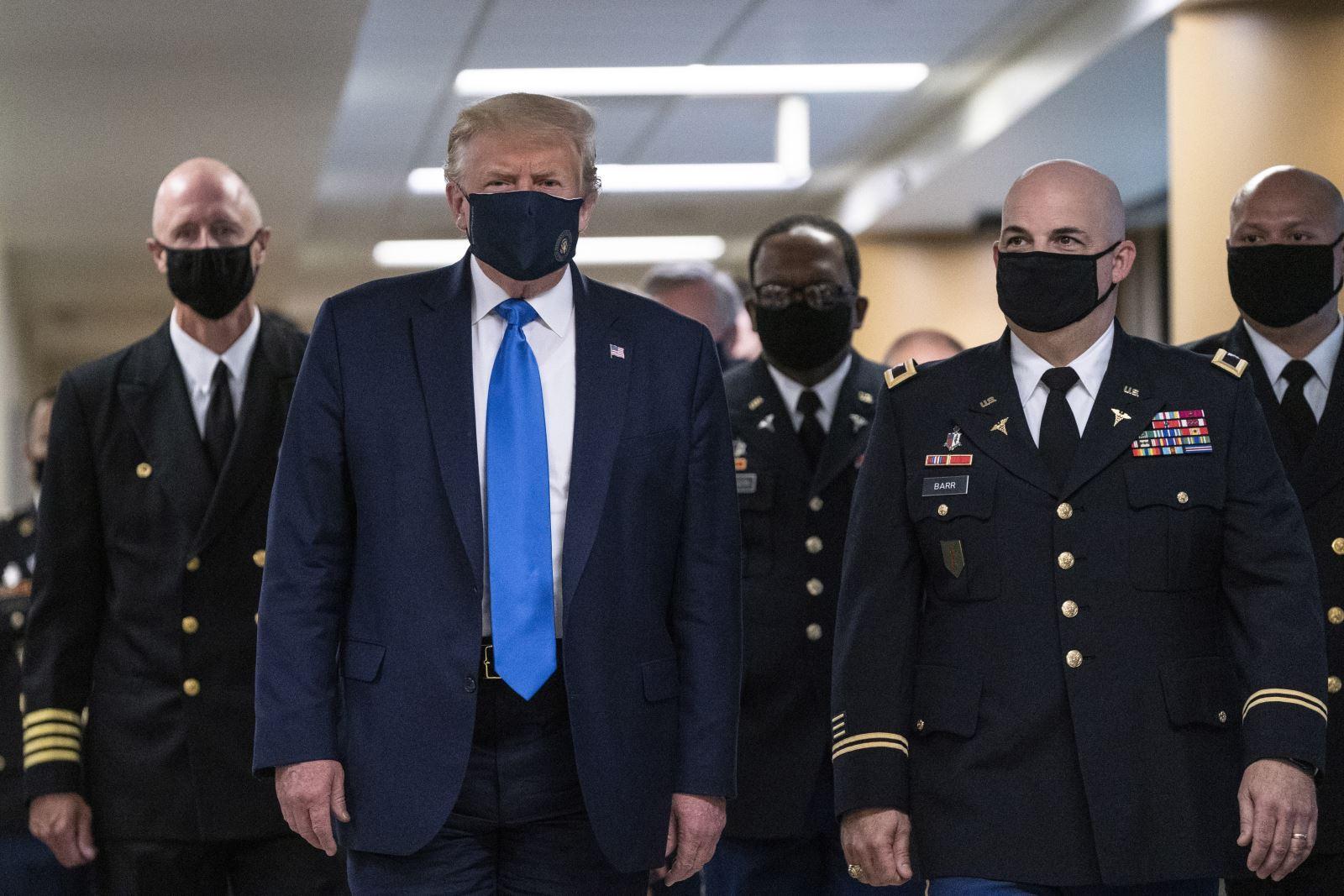 """Tổng thống Mỹ Donald Trump (trái, hàng đầu) nhấn mạnh: """"Tôi nghĩ đeo khẩu trang là điều cần thiết, nhất là khi nói chuyện với nhiều binh sĩ tại bệnh viện, trong đó một số trường hợp vừa rời khỏi bàn mổ"""". Ảnh: AFP/TTXVN"""