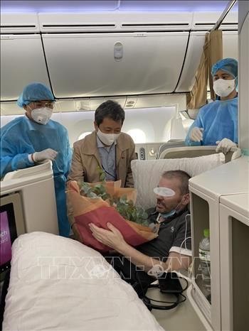 Đại sứ Việt Nam tại Anh Trần Ngọc An lên máy bay tặng hoa chúc mừng phi công người Anh, bệnh nhân số 91, bình phục và về đến Vương quốc Anh an toàn. Ảnh: TTXVN phát