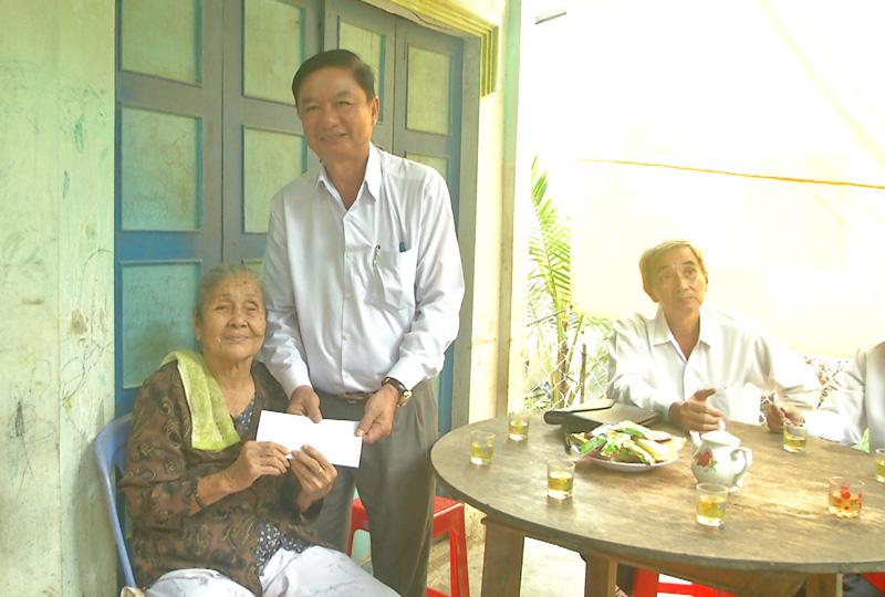 Bí thư Huyện ủy Lê Văn Khê trao quà cho mẹ Việt Nam anh hùng Trần Thị Út ở Quới Điền.