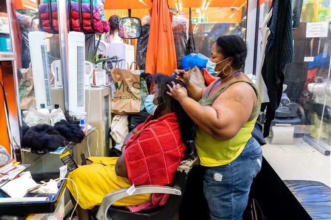 Người dân đeo khẩu trang tại một cửa hàng làm tóc ở Peckham, London, Anh, ngày 13-7-2020. Ảnh: AFP/TTXVN