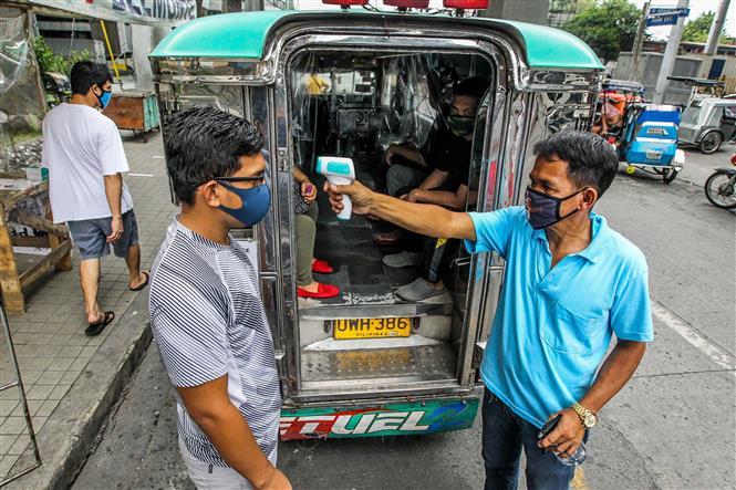 Tài xế xe Jeepney kiểm tra thân nhiệt cho hành khách tại Manila, Philippines, ngày 3-7-2020, trong bối cảnh dịch COVID-19 lan rộng. Ảnh: THX/ TTXVN