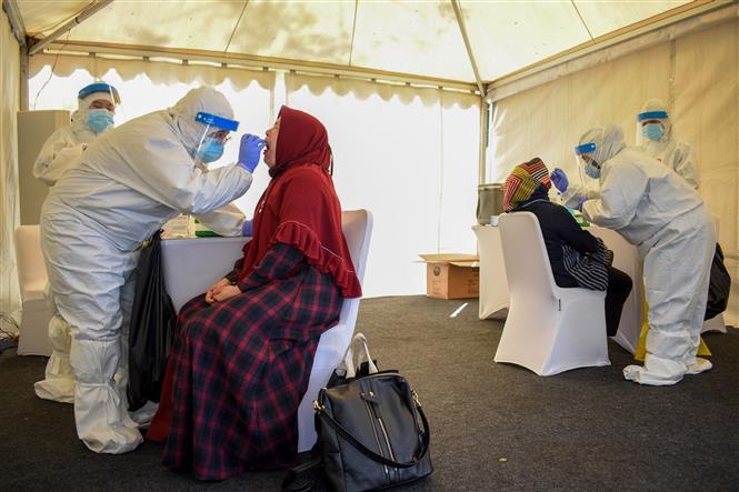Nhân viên y tế lấy mẫu dịch xét nghiệm COVID-19 cho người dân tại Bandung, Indonesia, ngày 11-7-2020. Ảnh: AFP/ TTXVN