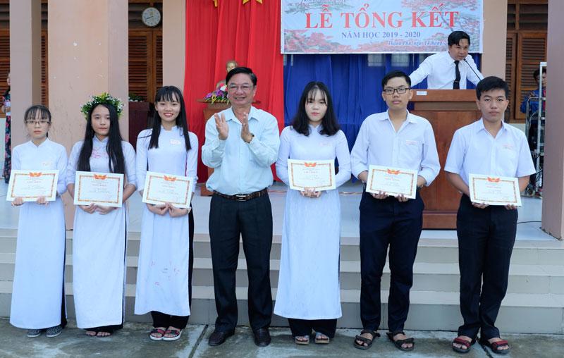 Bí thư Huyện ủy trao thưởng cho các em học sinh.