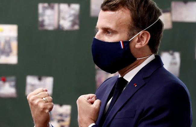 Tổng thống Emmanuel Macron đeo khẩu trang khi đến thăm trường tiểu học. Ảnh: Reuters