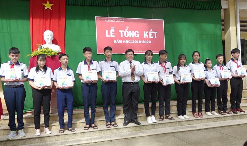Lãnh đạo huyện rao thưởng cho các em học sinh đạt thành tích cao. Ảnh: Việt Cường