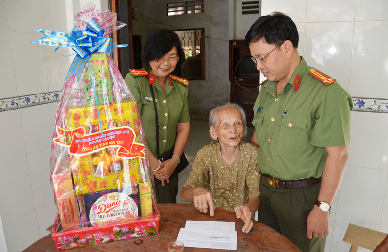 Phó giám đốc Công an tỉnh Phạm Thanh Tùng (bìa phải) thăm, tặng quà cho mẹ Việt Nam anh hùng Dương Thị Khối ở xã Tân Trung, huyện Mỏ Cày Nam.  Ảnh: Hải Đăng