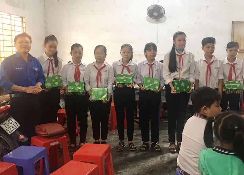 Ông Trần Quốc Thạnh - Bí thư Đoàn Cơ sở Công ty Điện lực Bến Tre (bìa trái) tặng quà cho các em học sinh có hoàn cảnh khó khăn.