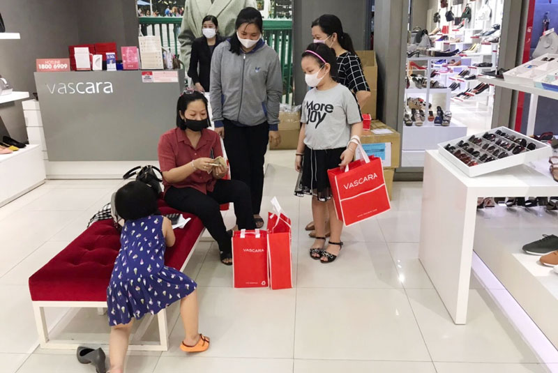 Người dân nâng cao ý thức đeo khẩu trang khi đi mua sắm, đến nơi công cộng. Ảnh: PV