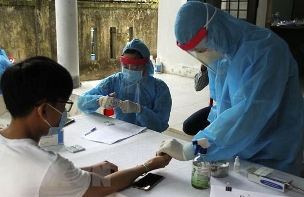 Các cán bộ y tế tiến hành xét nghiệm nhanh COVID-19 cho người dân trở về từ vùng có dịch. Ảnh: Hồ Cầu/TTXVN