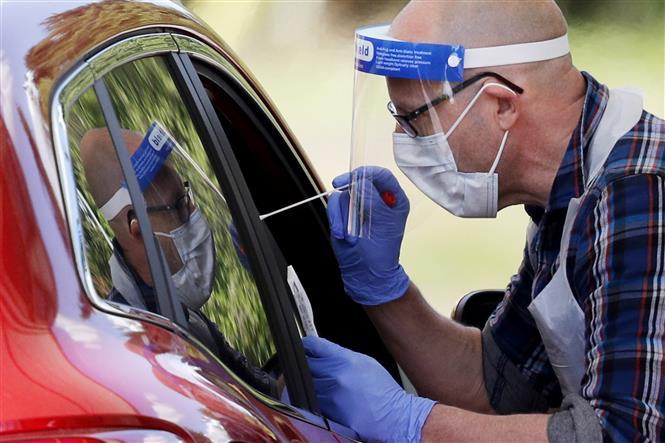 Nhân viên y tế lấy mẫu dịch xét nghiệm COVID-19 cho người dân tại Chessington, Anh ngày 2-5-2020. Ảnh: AFP/TTXVN