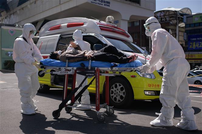 Nhân viên y tế chuyển bệnh nhân COVID-19 tới bệnh viện Đại học Keimyung ở Daegu, Hàn Quốc, ngày 12-3-2020. Ảnh: AFP/ TTXVN