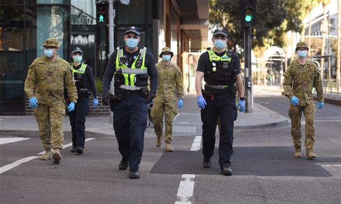 Cảnh sát và binh sĩ tuần tra tại một tuyến phố ở Melbourne, bang Victoria, Australia sau khi chính quyền địa phương áp dụng lệnh hạn chế mới nhằm ngăn chặn sự lây lan của dịch COVID-19, ngày 3-8-2020/2020. Ảnh: AFP/TTXVN