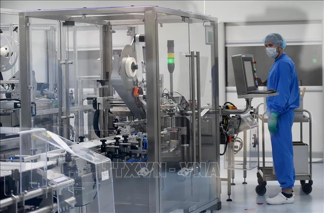Nhân viên làm việc trên dây chuyền sản xuất vaccine phòng COVID-19 tại một công ty công nghệ sinh học ở thành phố Saint Petersburg, Nga ngày 20-5-2020. Ảnh: AFP/TTXVN