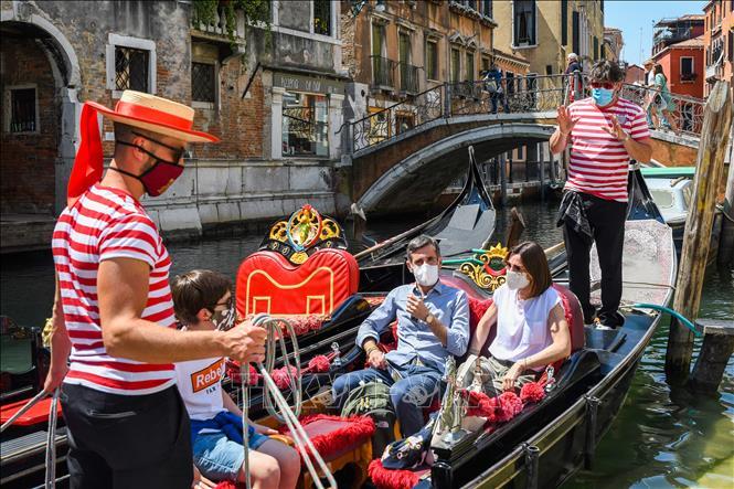 Du khách đeo khẩu trang phòng lây nhiễm COVID-19 tại Venice, Italy, ngày 12-6. Ảnh: AFP/TTXVN